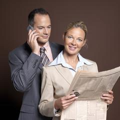 Geschäftsmann mit Handy, Geschäftsfrau mit Zeitung