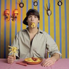 Junger Mann isst Pommes Frites