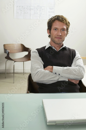 Young man sitting on desk, arms crossed