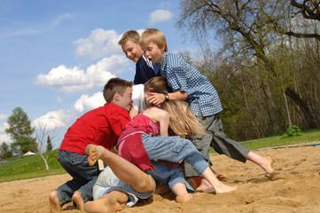 Kinder spielen am Spielplatz, kämpfen und raufen
