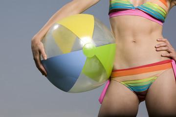 Junge Frau im Bikini hält Wasserball, tolle Figur
