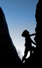 A rock climber climbs his way to the top