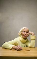 Ältere Dame Frau sitzen am Schreibtisch mit Bleistift