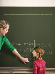Lehrer erklären Rechenaufgabe zu Mädchen