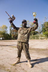 Paintball player with gun and gold cup