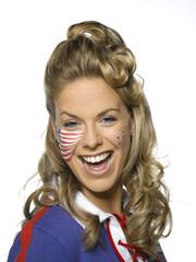 Junge Frau mit der amerikanischen Flagge, gemalt auf Gesicht, lächelnd