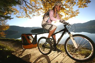 Frau Radfahren See mit Kind im Anhänger