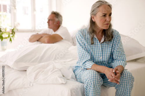 Mature couple sitting on bed (focus on woman in foreground)