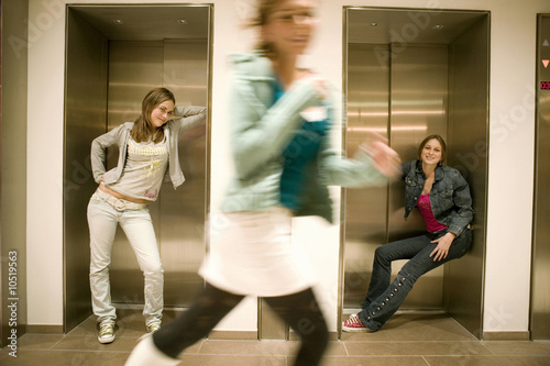 Two women leaning on lift door one woman running