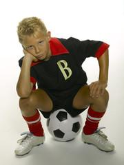 Junge sitzt auf einem Fußball