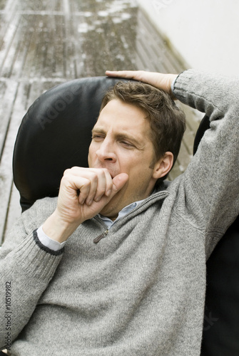 Man in an armchair yawning