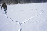 Man walking in snow, making heart shape by footprint