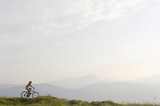 Austria, alps, woman riding bicycle on meadow