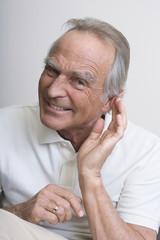 Senior Mann mit der Hand zum Ohr, Lächeln, Portrait