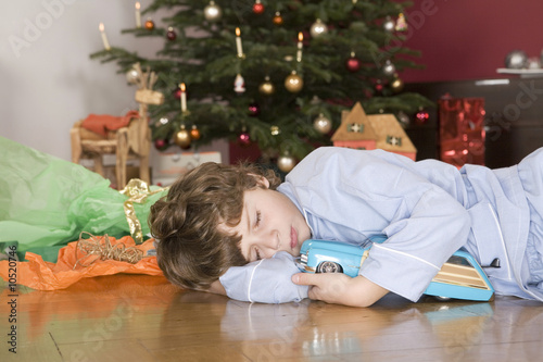 Boy (4-7) sleeping under Christmas tree, holding toy car