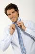 Junger Geschäftsmann Krawatte richten, close-up, Portrait