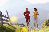 Young couple jogging by wooden fence, mountains in backgrounds
