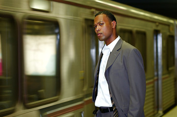 An African-American businessman awaits his commuter train