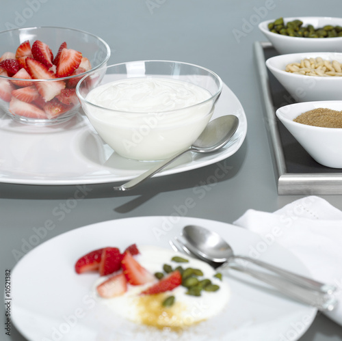 Yoghurt and strawberries in glass bowls on plate, close-up