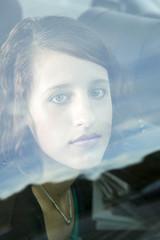 junge Frau schaut durch Fensterscheibe