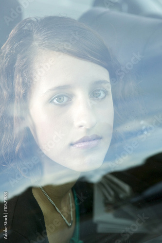 young woman looking through window pane, portrait
