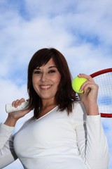 Beautiful female tennis player with racket and ball