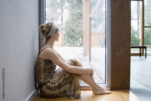 Ballerina sits on floor looking out of window
