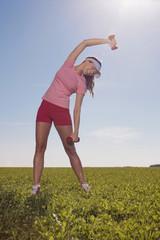 Frau jung mit der Hanteln heben, Stretching