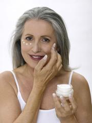 Frau, Seniorin auftragen Gesichtscreme, Portrait