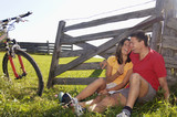 Couple sitting in meadow, leaning on wooden railing