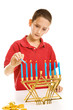 Young boy lighting the menorah for Hanukkah.  Isolated