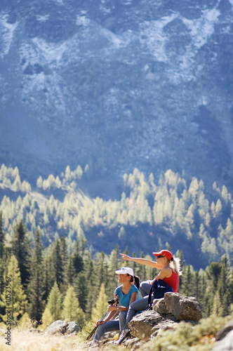 Two women sitting on rock in mountains, side view
