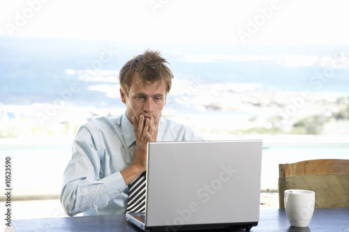 Man sitting at table, using laptop