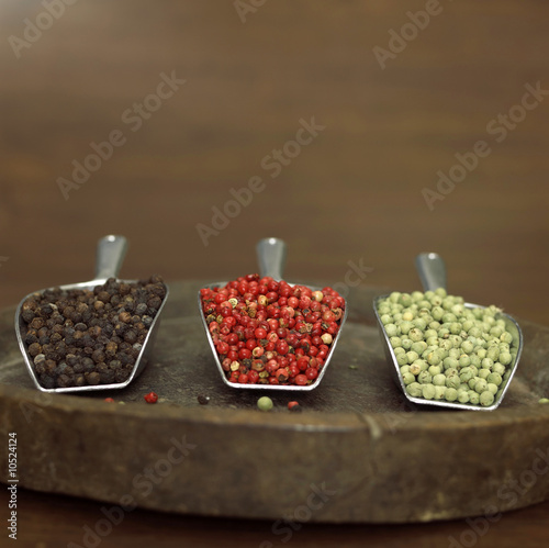 Red, green and black pepper on shovel