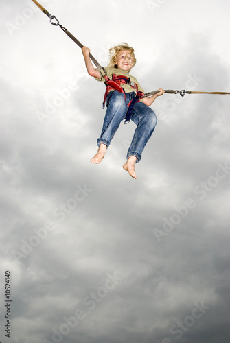 Boy (10-11) on bungee swing, smiling, low angle view