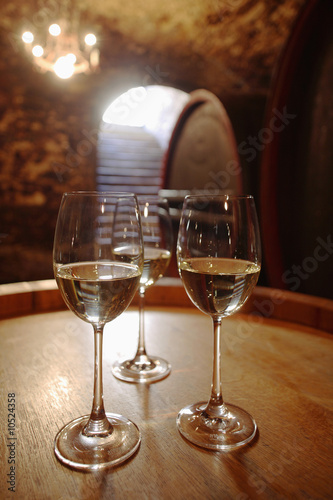 Wite wine in glasses on wine cask