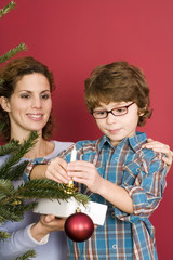 Mutter und Sohn schmücken Weihnachtsbaum, close-up