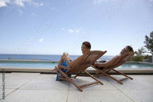 Paar sitzen in Liegestühle am Schwimmbecken