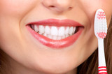 Fototapety Smiling  young woman with healthy teeth holding a tooth-brush.
