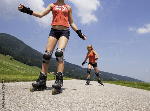 Two teenage girls (13-15) inline skating