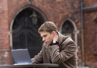 Young men hardly thinking near the laptop outside