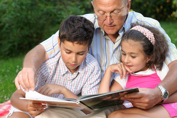 Grandfather,grandson and granddaughter reading a book