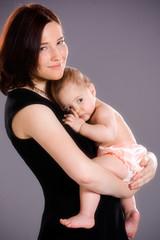 Smiling Mother Hugs Baby Girl