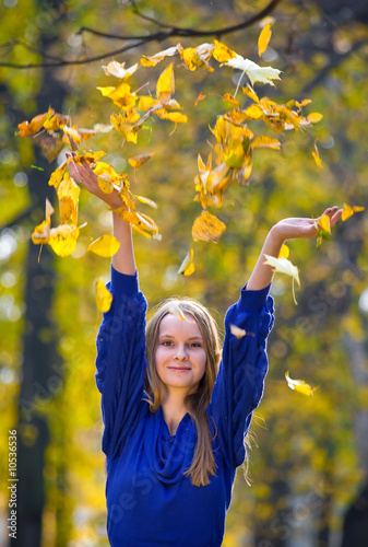 Young pretty girl throwing autumn leaves