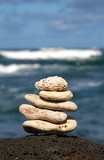 White coral rocks stacked by a meditating zen follower poster
