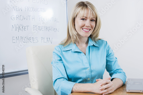 Woman Sitting in Front of Whiteboard
