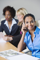 Businesswoman Using Cell Phone During meeting