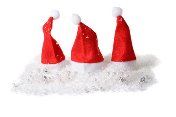 Three little christmas hats in the snow on white background