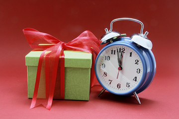 Alarm Clock and Gift Box on Red Background