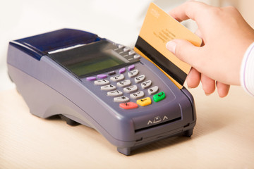 Close-up of hand putting credit card into payment machine
